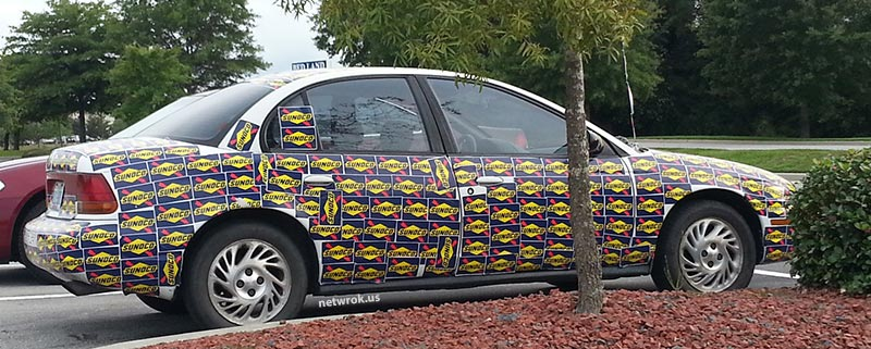 Car covered with Sunoco stickers in Walmart parking lot